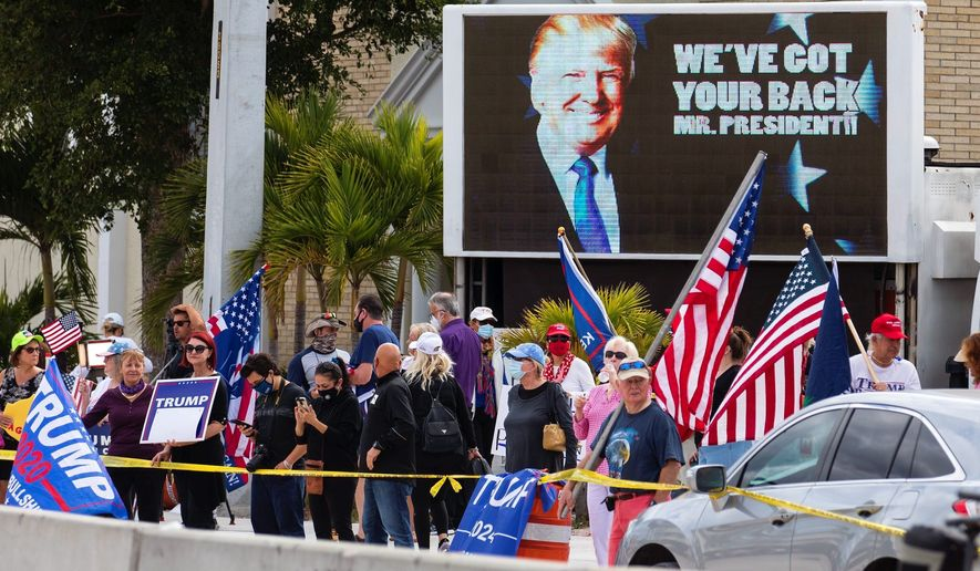 Former President Donald Trump's supporters greet him as his motorcade passes by on the road to Mar-a-Lago on Wednesday. (The Palm Beach Post via Associated Press)