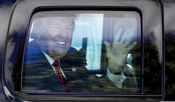 Former President Donald Trump waves to supporters as his motorcade drives through West Palm Beach, Fla., on his way to his Mar-a-Lago club in Palm Beach after arriving from Washington aboard Air Force One on Wednesday, Jan. 20, 2021. (Damon Higgins/The Palm Beach Post via AP)