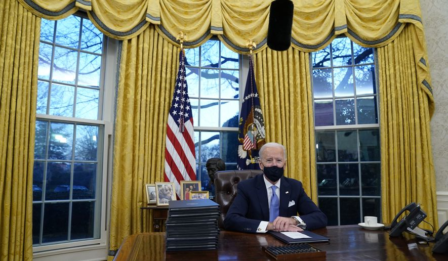 President Joe Biden pauses as he signs his first executive orders in the Oval Office of the White House on Wednesday, Jan. 20, 2021, in Washington.(AP Photo/Evan Vucci)
