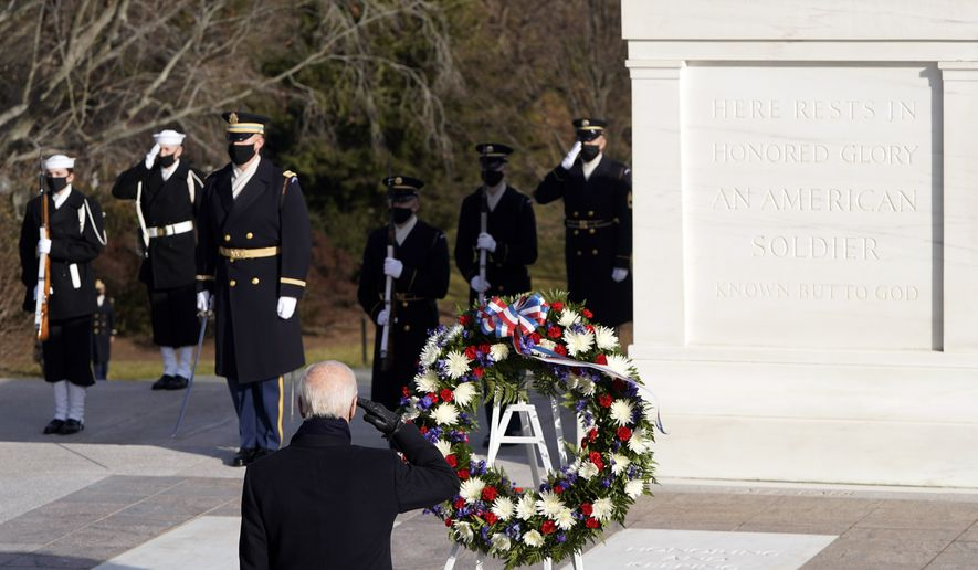 President Joe Biden salutes at the Tomb of the Unknown Soldier at the Arlington National Cemetery, in Arlington, Va., Wednesday, Jan. 21, 2021. Joshua Roberts/Pool photo via AP)