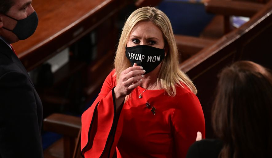 "In this Sunday, Jan. 3, 2021, file photo, Rep. Marjorie Taylor Greene, R-Ga., wears a ""Trump Won"" face mask as she arrives on the floor of the House to take her oath of office on opening day of the 117th Congress at the U.S. Capitol in Washington. (Erin Scott/Pool Photo via AP, File)"