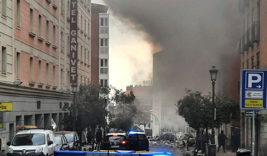 Smoke rises from a building and rubble scattered in Toledo Street following a explosion in downtown Madrid, Spain, Wednesday, Jan. 20, 2021. A loud explosion of unknown origin has partially destroyed a six-floor-tall building flanked by a school and a nursing home in the center of Spain's capital, Madrid. (Europa Press via AP)