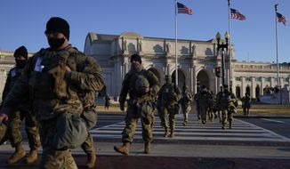National Guards walk from Union Station to the U.S. Capitol as events get underway for President-elect Joe Biden's inauguration ceremony, Wednesday, Jan. 20, 2021, in Washington. (AP Photo/John Minchillo) ** FILE **