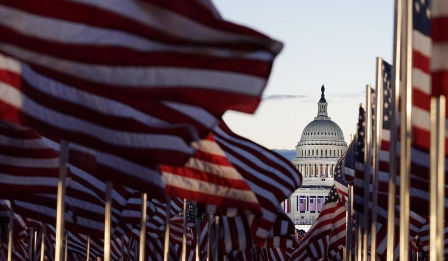 Flags line the National Mall towards the Capitol Building as events get underway for President-elect Joe Biden's inauguration ceremony, Wednesday, Jan. 20, 2021, in Washington. (AP Photo/Julio Cortez)