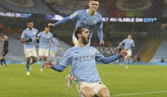 Manchester City's Phil Foden celebrates after scoring his side's opening goal during the English Premier League soccer match between Manchester City and Aston Villa at the Etihad Stadium in Manchester, England, Wednesday, Jan.20, 2021. (Martin Rickett/Pool via AP)