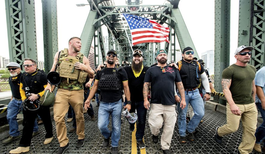 Members of the Proud Boys, including organizer Joe Biggs, third from right, march across the Hawthorne Bridge during an 'End Domestic Terrorism' rally in Portland, Ore., on Saturday, Aug. 17, 2019.  (AP Photo/Noah Berger, file)