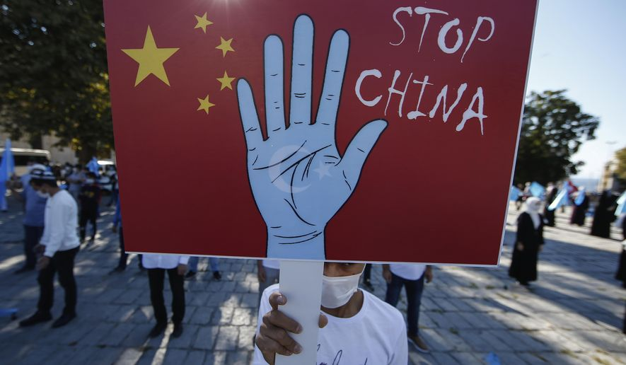 In this file photo taken Thursday, Oct. 1, 2020, a protester from the Uighur community living in Turkey, holds an anti-China placard during a protest in Istanbul against what they allege is oppression by the Chinese government to Muslim Uighurs in far-western Xinjiang province. The accusation of genocide by U.S. Secretary of State Mike Pompeo against China touches on a hot-button human rights issue between China and the West. (AP Photo/Emrah Gurel, File)