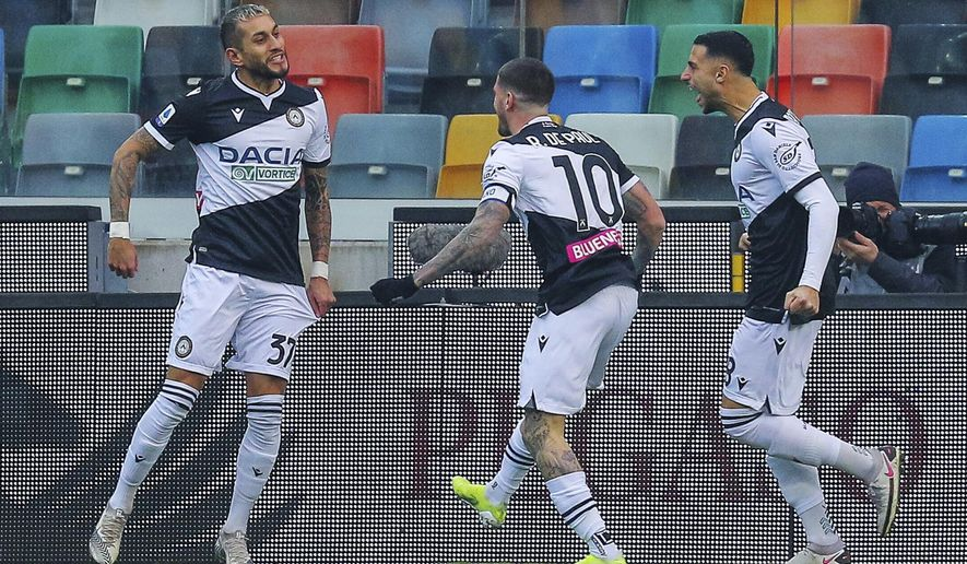Udinese's Roberto Pereyra, left, is congratulated by teammates after scoring his side's first goal during the Serie A soccer match between Udinese and Atalanta at the Dacia Arena Stadium in Udine, Italy, Wednesday, Jan. 20, 2021. (Andrea Bressanutti/LaPresse via AP)
