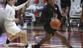 Louisville's Dana Evans, right, escapes Virginia Tech's Georgia Amoore after stealing the ball from her in the final moments of an NCAA college basketball game Thursday, Jan. 7, 2021, in Blacksburg, Va. (Matt Gentry/The Roanoke Times via AP, Pool)