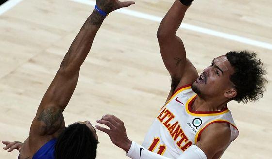 Atlanta Hawks guard Trae Young (11) shoots as Detroit Pistons guard Derrick Rose (25) defends during the first half of an NBA basketball game Wednesday, Jan. 20, 2021, in Atlanta. (AP Photo/John Bazemore)