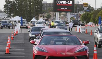 People wait in their vehicles to monitor for adverse reactions to the shot, after being vaccinated at a mass COVID-19 vaccination site outside The Forum in Inglewood, Calif., Tuesday, Jan. 19, 2021. California has become the first state to record more than 3 million known coronavirus infections, according to a tally Monday by Johns Hopkins University.  (AP Photo/Damian Dovarganes)