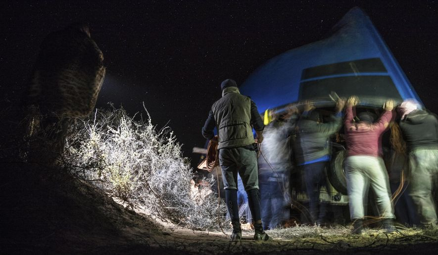 """Smugglers lift onto a vehicle a fishing boat intended to be used to transport migrants to the Canary Islands, in a remote desert out of the town of Dakhla in Morocco-administered Western Sahara, Tuesday, Dec. 22, 2020. Migrant smugglers recently tried to retrieve a boat buried in the Sahara sand. It was a made-to-order vessel built to carry migrants from the North African coast to Spain's Canary Islands. That's a journey that the European Union calls """"the most dangerous migratory route in the world."""" The Associated Press witnessed the recent boat handover, a crucial but little-seen piece of the migrant smuggling business. (AP Photo/Mosa'ab Elshamy)"""