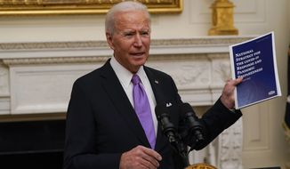 President Joe Biden holds a booklet as he speaks about the coronavirus in the State Dinning Room of the White House, Thursday, Jan. 21, 2021, in Washington. (AP Photo/Alex Brandon)