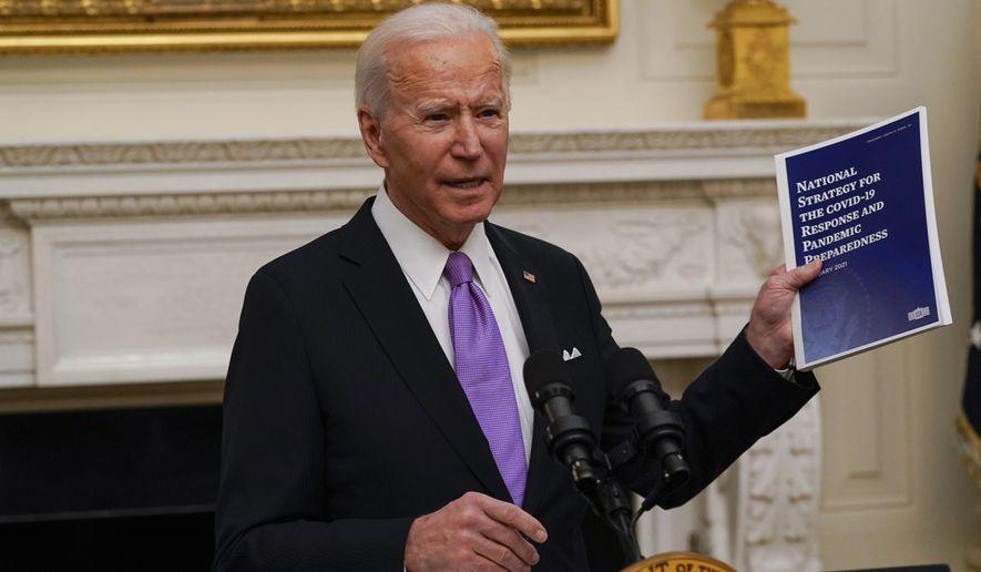 President Joe Biden holds a booklet as he speaks about the coronavirus in the State Dinning Room of the White House, Thursday, Jan. 21, 2021, in Washington. (AP Photo/Alex Brandon)
