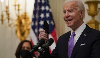 President Joe Biden holds a face mask as he speaks about the coronavirus in the State Dinning Room of the White House, Thursday, Jan. 21, 2021, in Washington. (AP Photo/Alex Brandon)