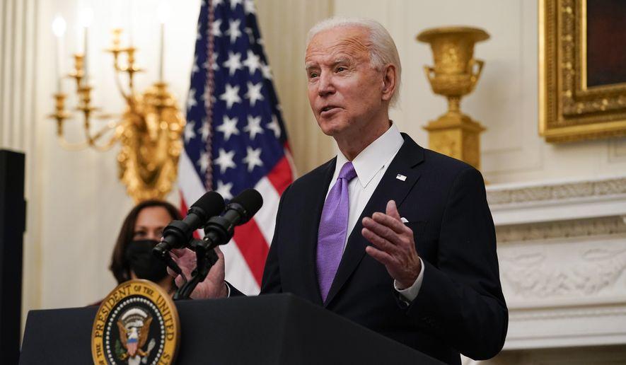 President Joe Biden speaks about the coronavirus, accompanied by Vice President Kamala Harris, in the State Dinning Room of the White House, Thursday, Jan. 21, 2021, in Washington. (AP Photo/Alex Brandon)