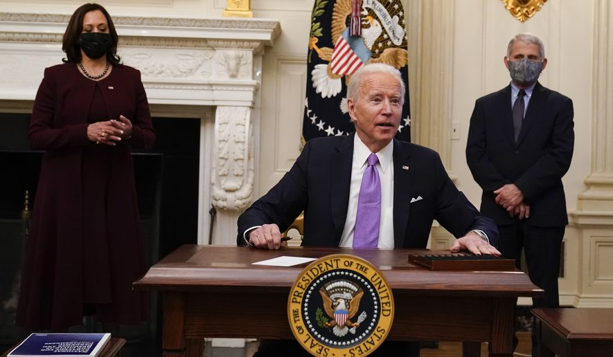 President Joe Biden reacts to a reporters question after signing executive orders in the State Dinning Room of the White House, Thursday, Jan. 21, 2021, in Washington. Vice President Kamala Harris, left, and Dr. Anthony Fauci, director of the National Institute of Allergy and Infectious Diseases, right, look on. (AP Photo/Alex Brandon)