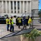 Workers disassemble metal fences that wrapped around the National Archives Museum on Thursday in the District. The fences were part of security efforts for Inauguration Day. (Emily Zantow/The Washington Times)