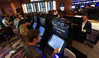 "FILE - In this March 11, 2020, file photo, patrons place in person bets during the launch of legalized sports betting in Michigan at the MGM Grand Detroit casino in Detroit. Online sports betting and casino games will start in Michigan at noon Friday, Jan. 22, 2021, an expansion of options for gamblers who now wager through offshore sites. State regulators have authorized licenses for all three Detroit casinos and seven of the dozen tribes with ""Class III"" casinos. (AP Photo/Paul Sancya, File)"