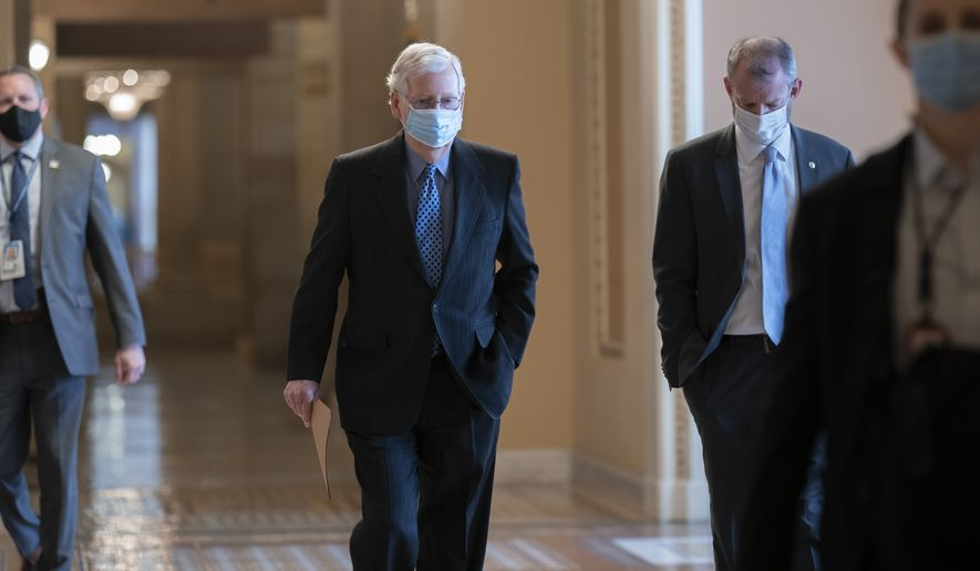On the first full day of the new Democratic majority in the Senate, Sen. Mitch McConnell, R-Ky., the top Republican, walks to the chamber for the start of business as the minority leader, at the Capitol in Washington, Thursday, Jan. 21, 2021. There is now a 50-50 split between Republicans and Democrats, but with Democratic Vice President Kamala Harris as the tie-breaker, the majority shifts by the slimmest of margins. (AP Photo/J. Scott Applewhite)