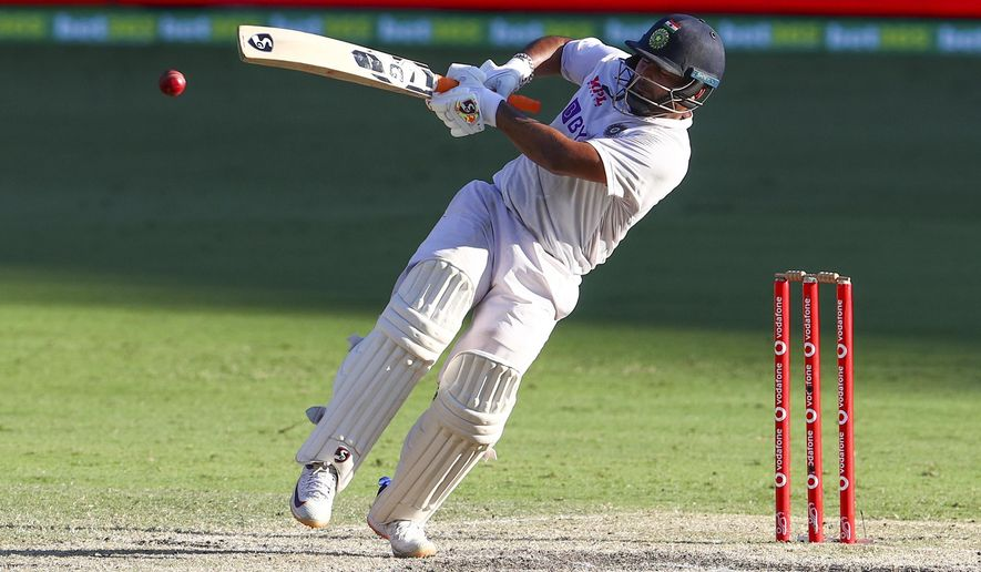 India's Rishabh Pant falls as he hits the ball for four runs during play on the final day of the fourth cricket test between India and Australia at the Gabba, Brisbane, Australia, Tuesday, Jan. 19, 2021. (AP Photo/Tertius Pickard)