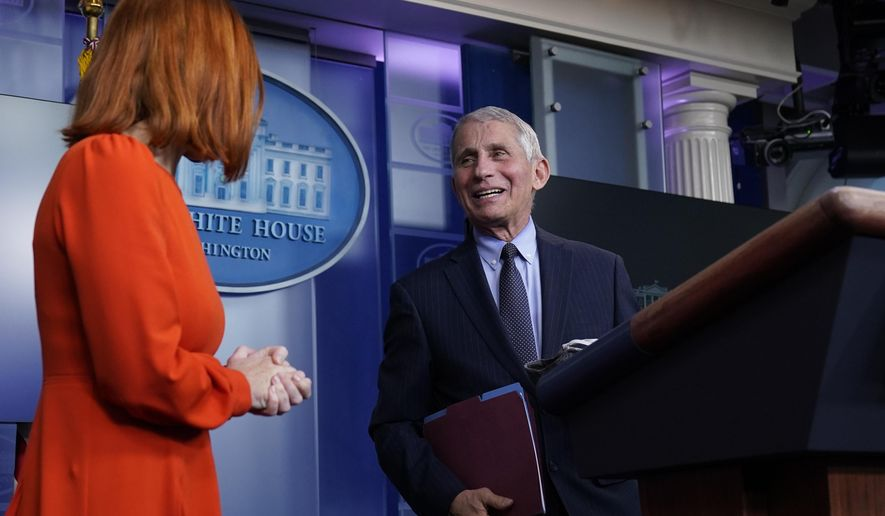 White House press secretary Jen Psaki speaks with Dr. Anthony Fauci, director of the National Institute of Allergy and Infectious Diseases, during a press briefing in the James Brady Press Briefing Room at the White House, Thursday, Jan. 21, 2021, in Washington. (AP Photo/Alex Brandon)