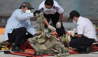 Investigators inspect a pieces of the Sriwijaya Air flight SJ-182 retrieved from the Java Sea where the passenger jet crashed on Jan. 9, at Tanjung Priok Port in Jakarta, Indonesia, Thursday, Jan. 21, 2021. Indonesian authorities on Thursday ended the search for the wreckage of the plane that nose-dived into the sea, killing all of its passengers on board. (AP Photo/Dita Alangkara)
