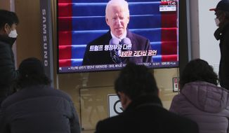 """People watch a TV screen showing a news report about U.S. President Joe Biden's inauguration, at the Seoul Railway Station in Seoul, South Korea, Thursday, Jan. 21, 2021. The sign reads """"New leadership."""" (AP Photo/Ahn Young-joon)"""