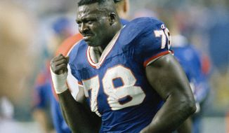 FILE - IN this Jan. 30, 1994 file photo, Buffalo Bills' Bruce Smith holds up his injured hand during the third quarter of Super Bowl XXVIII against the Dallas Cowboys in Atlanta.   Smith is happy seeing the Buffalo Bills finally back in the AFC championship game for the first time in 27 years. What excites him more is a belief the team seems poised for long-term success in drawing comparisons of Buffalo's team in 1988, which would eventually go on to make, and lose, four straight Super Bowl appearances starting in '91. (AP Photo /John J. Gaps III, File)