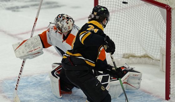 Boston Bruins left wing Jake DeBrusk (74) scores against Philadelphia Flyers goaltender Carter Hart (79) during a shootout in an NHL hockey game, Thursday, Jan. 21, 2021, in Boston. The Bruins won 5-4 in a shootout. (AP Photo/Elise Amendola)