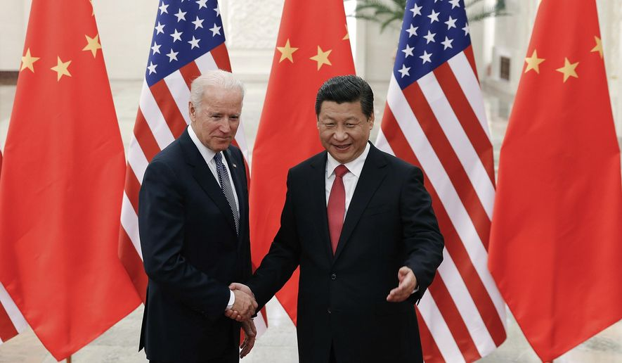 In this Dec. 4, 2013, file photo, Chinese President Xi Jinping, right, shakes hands with then U.S. Vice President Joe Biden as they pose for photos at the Great Hall of the People in Beijing. (AP Photo/Lintao Zhang, Pool, File)