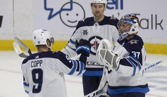 Winnipeg Jets' Neal Pionk, rear, Andrew Copp, and goaltender Connor Hellebuyck celebrate the team's win over the Ottawa Senators in an NHL hockey game Thursday, Jan. 21, 2021, in Ottawa, Ontario. (Adrian Wyld/The Canadian Press via AP)