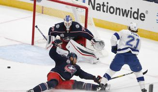 Columbus Blue Jackets' Seth Jones, front left, knocks the puck away from Tampa Bay Lightning's Brayden Point, as Blue Jackets' Joonas Korpisalo, of Finland, protects the net during the first period of an NHL hockey game Thursday, Jan. 21, 2021, in Columbus, Ohio. (AP Photo/Jay LaPrete)