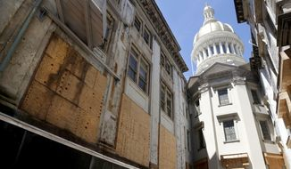 FILE - In this May 24, 2018, file photo, windows are seen boarded up during the renovation of the New Jersey Statehouse, in Trenton, N.J. The $300 million refurbishment that began soon after it was announced by former Gov. Chris Christie in late 2016 was supposed to take four years. In 2018, the completion date was expected to be 2022, and now Gov. Phil Murphy's administration says it'll be January 2023 before the renovation is done. (AP Photo/Julio Cortez, File)