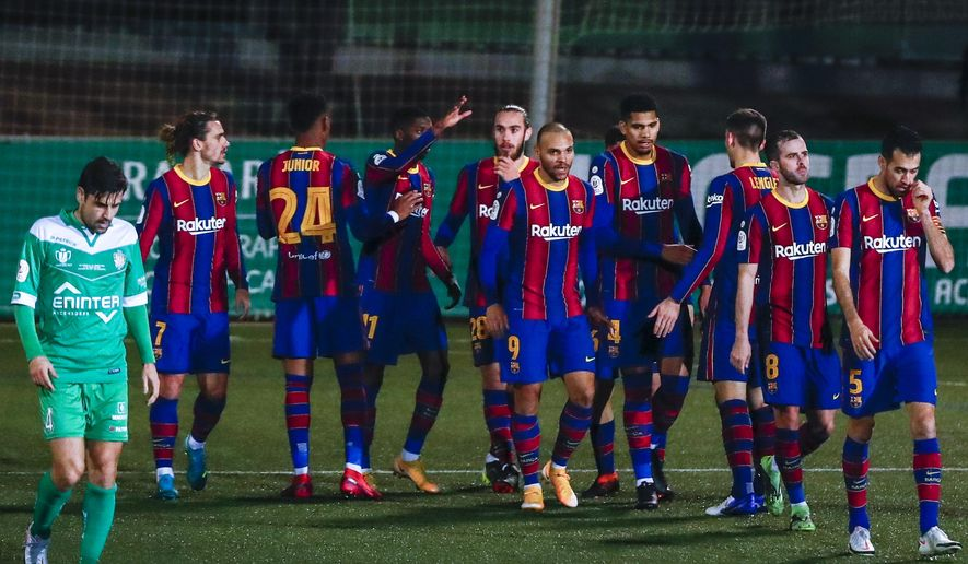 Barcelona players celebrate after Barcelona's Ousmane Dembele scored his side's first goal during a Spanish Copa del Rey round of 32 soccer match between Cornella and FC Barcelona at the Nou Municipal stadium in Cornella, Spain, Thursday, Jan. 21, 2021. (AP Photo/Joan Monfort)