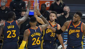 Golden State Warriors guard Stephen Curry (30) celebrates after scoring against the San Antonio Spurs with forward Draymond Green (23), forward Kent Bazemore (26) and forward Kevon Looney (5) during the first half of an NBA basketball game in San Francisco, Wednesday, Jan. 20, 2021. (AP Photo/Jeff Chiu)
