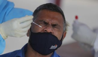 Sri Lankan municipal health workers take a swab sample from a man to test for COVID-19 in Colombo, Sri Lanka, Thursday, Jan. 21, 2021. Sri Lanka on Thursday re-opened the country for tourists after keeping the doors closed for the visitors for nearly 10 months due to the COVID-19. (AP Photo/Eranga Jayawardena)