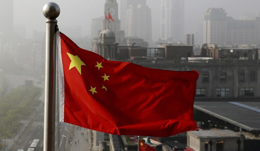A Chinese national flag flutters against the office buildings in Shanghai, China. (AP Photo/Andy Wong, File)