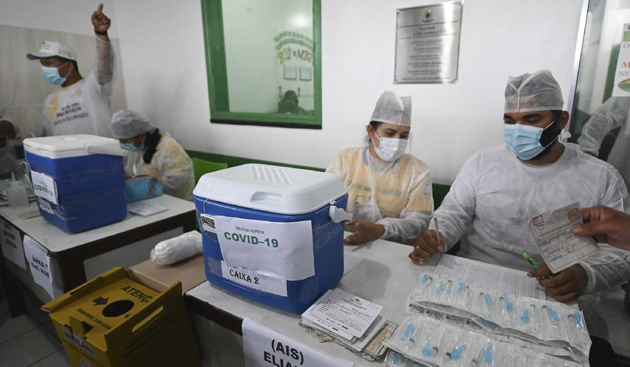 Health workers prepare doses of the COVID-19 vaccine produced by China's Sinovac Biotech Ltd., during the start of the vaccination plan on indigenous lands at the Ticuna de Umariacu village health post in Tabatinga, Amazonas state, Brazil, Tuesday, Jan. 19, 2021. (AP Photo/Andre Borges)