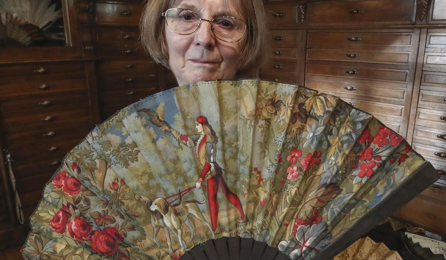 Anne Hoguet, 74, fan maker and director of the hand fan-making museum poses with a wood roasted hand fan representing a falcon hunt, gouache painting g on paper from 1880 at the museum in Paris, Wednesday, Jan. 20, 2021. Just like the leaves of its gilded fans, France's storied hand fan-making museum could fold up and vanish. The splendid Musee de l'Eventail in Paris, a classed historical monument, is the culture world's latest coronavirus victim. (AP Photo/Michel Euler)