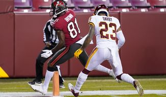 Tampa Bay Buccaneers wide receiver Antonio Brown (81) scores a touchdown against Washington Football Team cornerback Ronald Darby (23) during the first half of an NFL wild-card playoff football game, Saturday, Jan. 9, 2021, in Landover, Md. (AP Photo/Andrew Harnik)