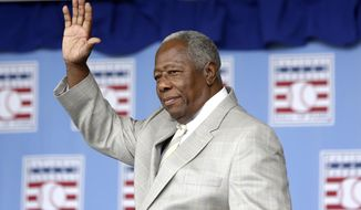 Hall of Famer Hank Aaron waves to the crowd during Baseball Hall of Fame induction ceremonies in Cooperstown, N.Y., in this Sunday, July 28, 2013, file photo. Hank Aaron, who endured racist threats with stoic dignity during his pursuit of Babe Ruth but went on to break the career home run record in the pre-steroids era, died early Friday, Jan. 22, 2021. He was 86. The Atlanta Braves said Aaron died peacefully in his sleep. No cause of death was given. (AP Photo/Mike Groll, File) **FILE**