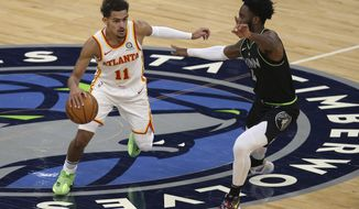 Atlanta Hawks' Trae Young (11) handles the ball as Minnesota Timberwolves' Jaylen Nowell (4) defends during the first half of an NBA basketball game Friday, Jan. 22, 2021, in Minneapolis. (AP Photo/Stacy Bengs)