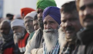 Indian Farmers listen to their leader as they continue to block highway leading to Delhi in protest against new farm laws, at Delhi-Uttar Pradesh border, India, Friday, Jan. 22, 2021. Talks between protesting farmers' leaders and the government ended abruptly in a stalemate on Friday with the agriculture minister saying he has nothing more to offer than suspending contentious agricultural laws for 18 months. The farmers' organizations in a statement on Thursday said they can't accept anything except the repeal of the three new laws. (AP Photo/Manish Swarup)