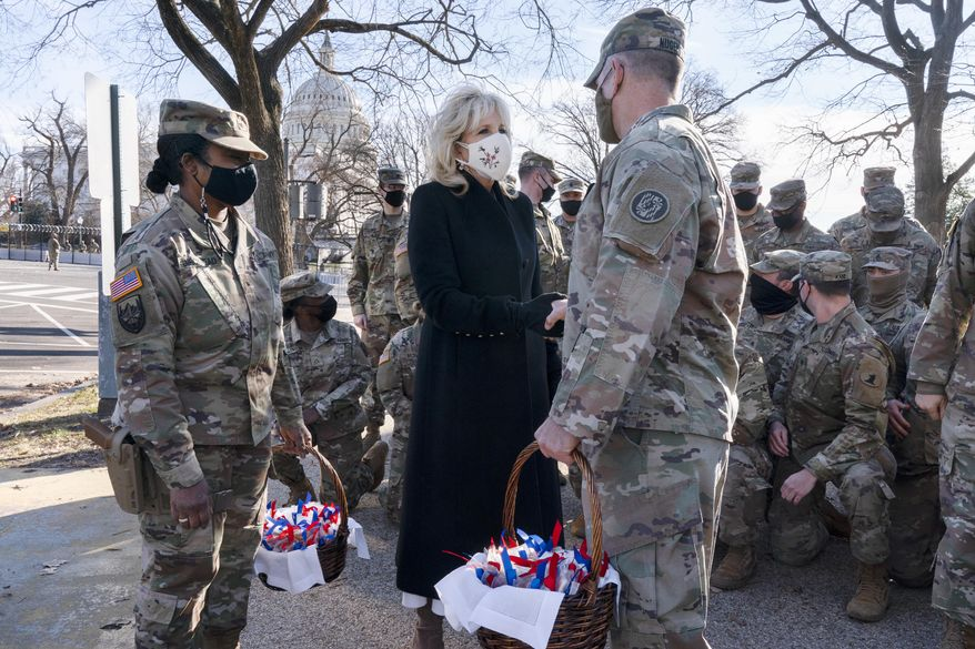 """Saying, """"The Biden's are a National Guard family,"""" first lady Jill Biden greets members of the National Guard with chocolate chip cookies, Friday, Jan. 22, 2021, at the U.S. Capitol in Washington.(AP Photo/Jacquelyn Martin, Pool)"""