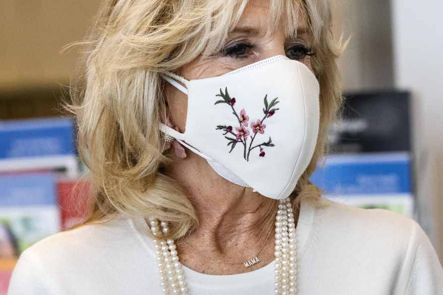 """First lady Jill Biden's necklace says """"Mama,"""" as she takes a tour of Whitman-Walker Health, Friday, Jan. 22, 2021, in Washington.(AP Photo/Jacquelyn Martin, Pool)"""