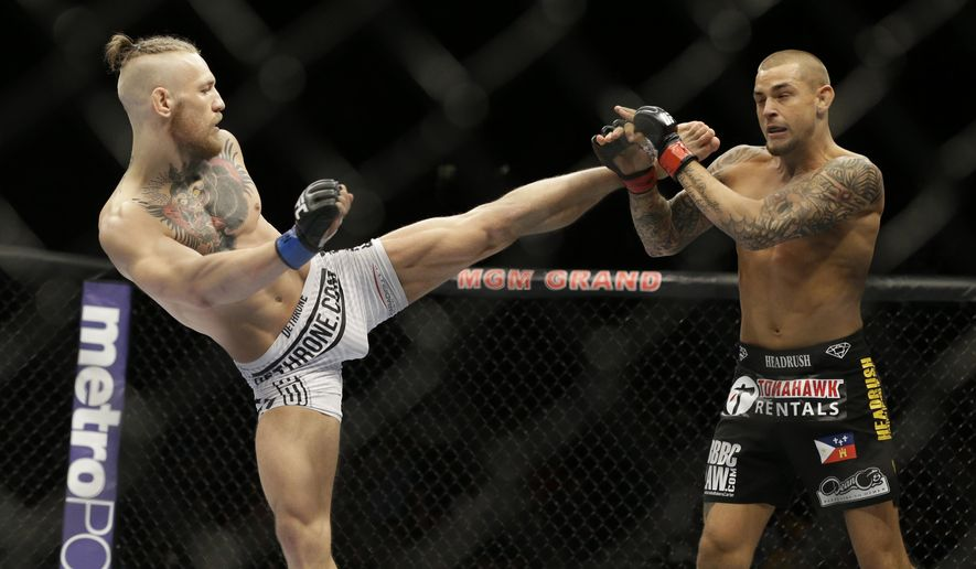 FILE - In this Sept. 27, 2014, file photo, Conor McGregor, left, kicks Dustin Poirier during their mixed martial arts bout in Las Vegas. McGregor returns from a year-long layoff for a rematch against Poirier in the promotions's first pay-per-view of the year, at UFC 257 on Jan. 24 at Abu Dhabi. (AP Photo/John Locher, File)