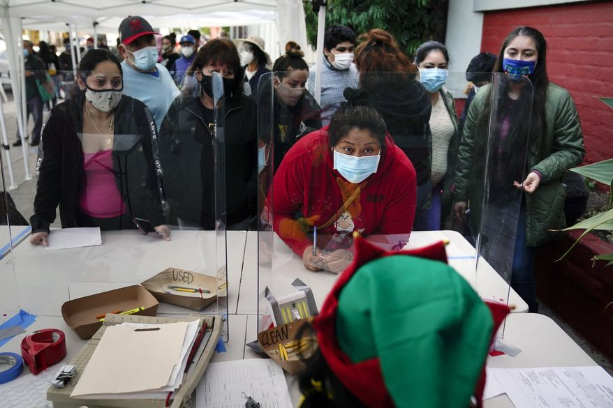 In this Dec. 17, 2020, file photo, people check in at a food bank held at Los Angeles Boys & Girls Club in the Lincoln Heights neighborhood of Los Angeles. California's unemployment rate edged up nearly 1 percentage point last month as the state shed more than 52,000 jobs led by the pandemic-hobbled restaurant and lodging industries, the state's beleaguered Employment Development Department reported Friday, Jan. 22, 2021. (AP Photo/Jae C. Hong, File)