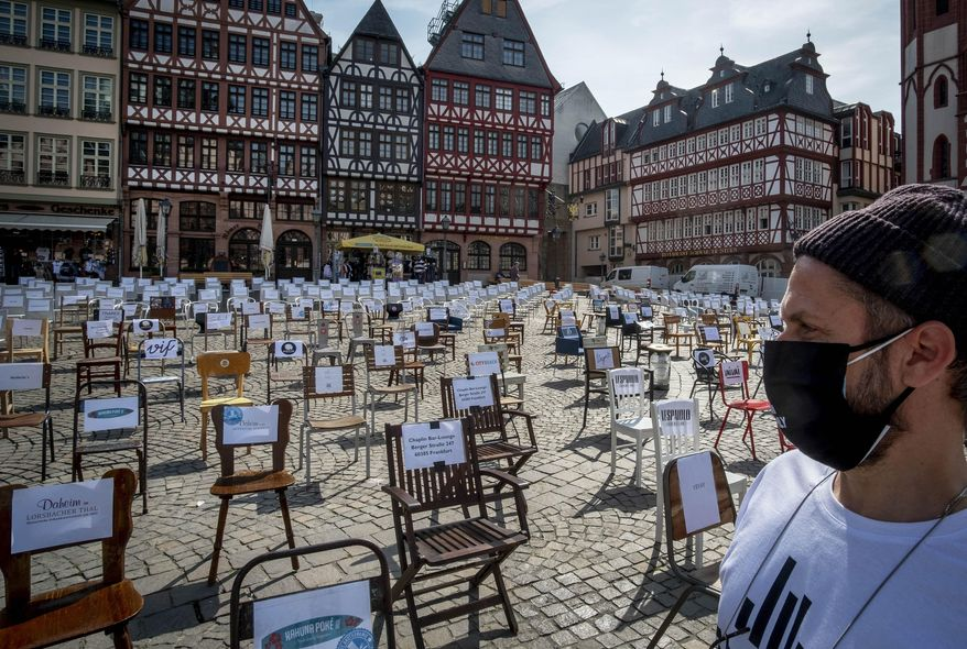 In this April 24, 2020, file photo, a man with a face mask watches empty chairs with names of bars and restaurants on the Roemerberg square in Frankfurt, Germany. More than 50,000 people have died after contracting COVID-19 in Germany, a number that has risen swiftly over recent weeks as the country has struggled to bring down infection figures. (AP Photo/Michael Probst, File)