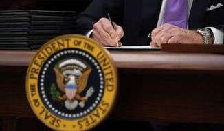 FILE - In this Jan. 21, 2021, file photo President Joe Biden signs executive orders after speaking about the coronavirus in the State Dinning Room of the White House in Washington. (AP Photo/Alex Brandon, File)